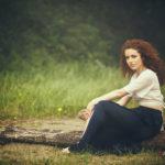 Modelo sentada en un tronco