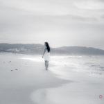 Mujer de paseo en playa solitaria
