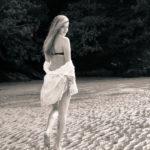 Caminando por la playa en bikini y con blusa