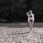 Mujer pasea por una playa desierta