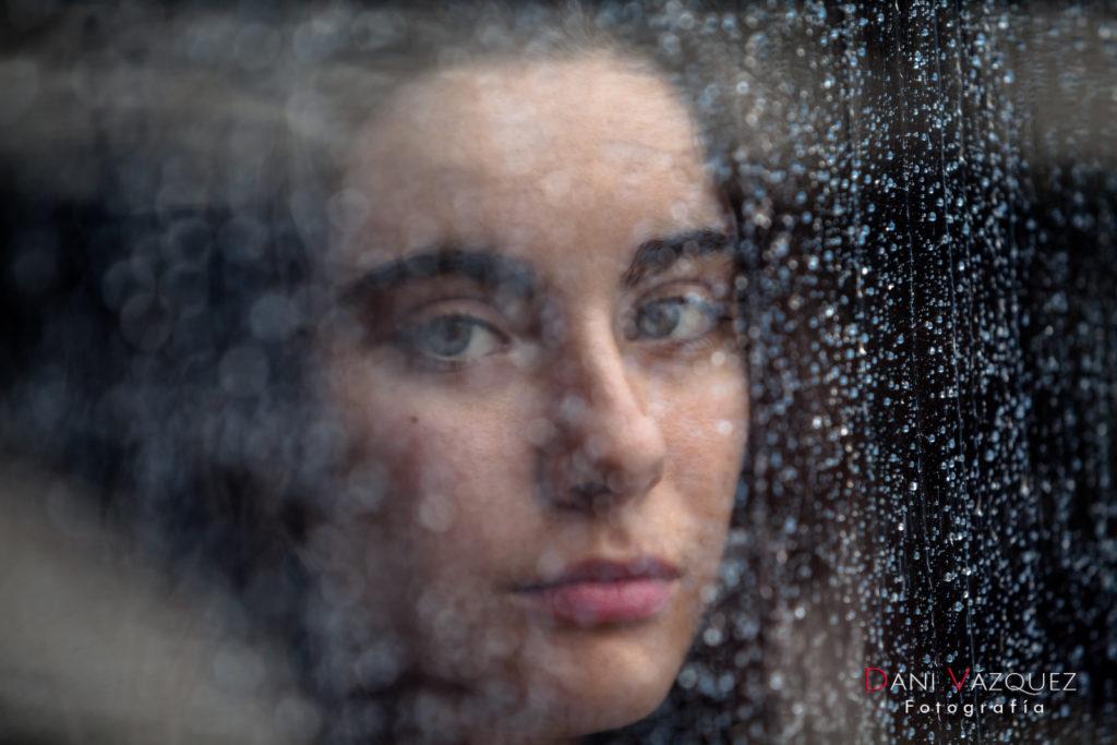 Mirada tras gotas de lluvia en la ventana