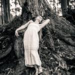 Modelo rubia posando en las raíces de un árbol