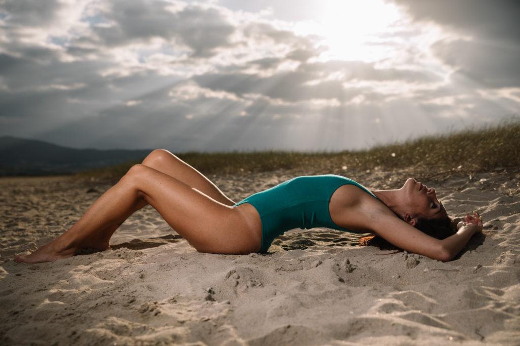 Chica en la playa y rayos de sol al fondo