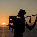 Gaiteiro tocando y puesta de sol