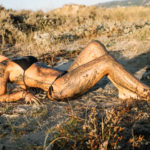 Baño de lodo de una mujer con el pelo rubio rizado