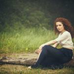 Chica pelirroja con melena rizada sentada en tronco