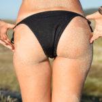 Mujer con la piel cubierta de arena