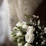 Ramo de flores blancas junto al vestido de novia