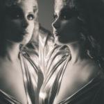 Modelo delante del espejo del estudio de maquillaje